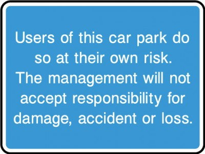 Cars Parked at own risk sign